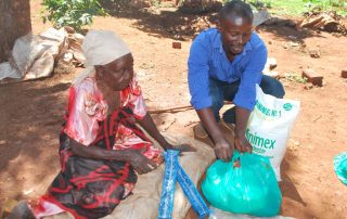 Ronnie opening a bag of food and supplies for Kigongo