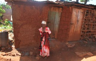 Kigongo stands in front of her house