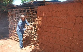 Ronnie repairing Kigongo's house