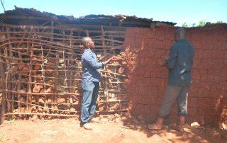 Ronnie and Fred repairing Kigongo's house